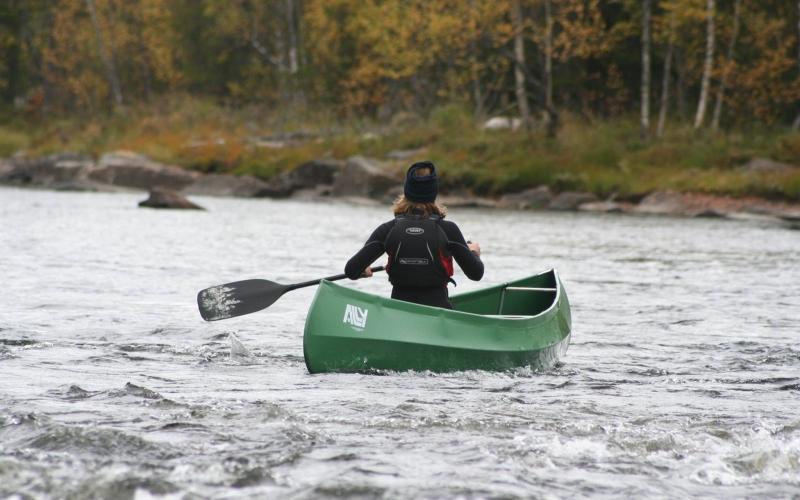 Jente som padler kano i elv.