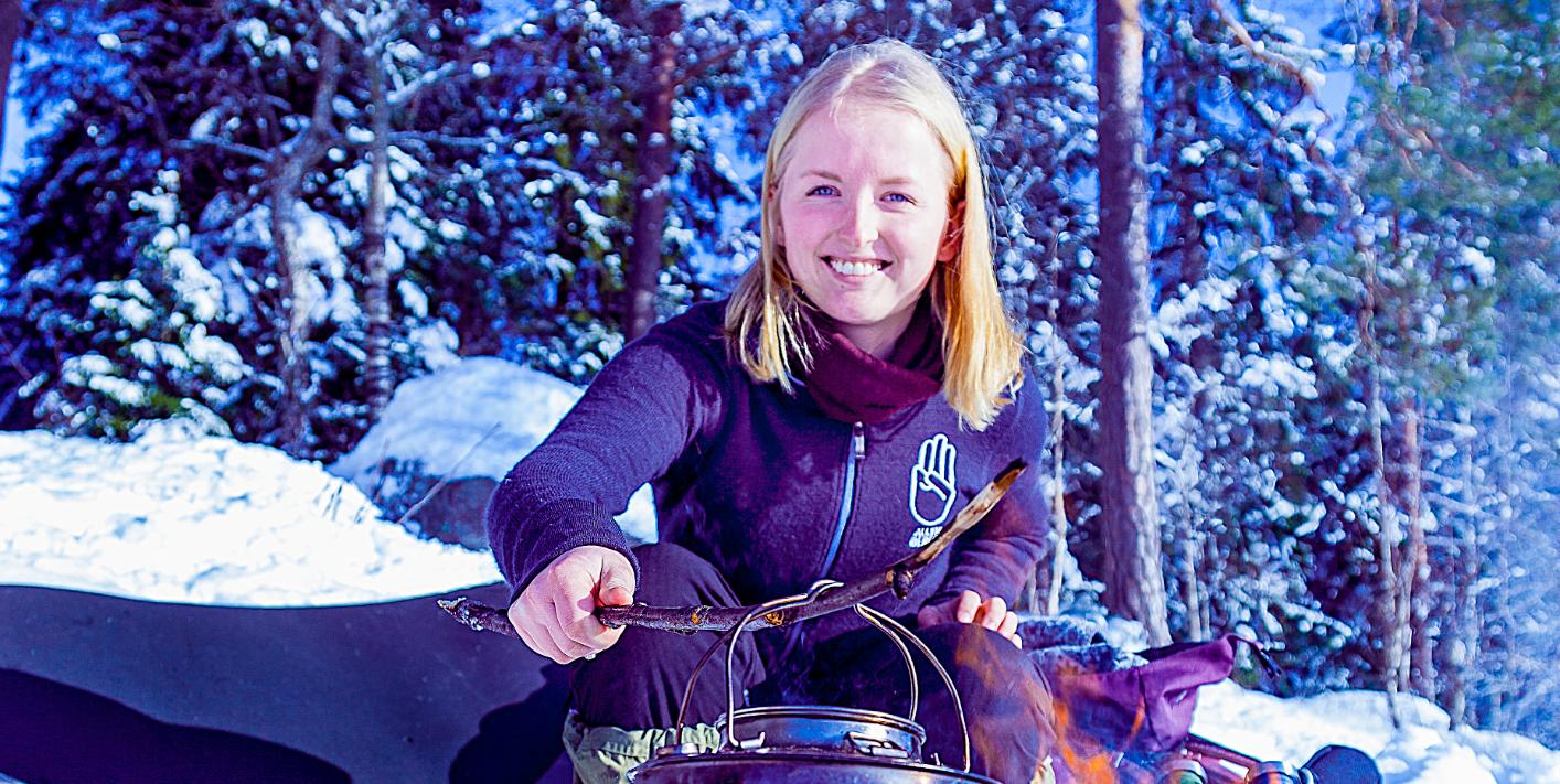 Bilde av en jente som koker kaffe på bål